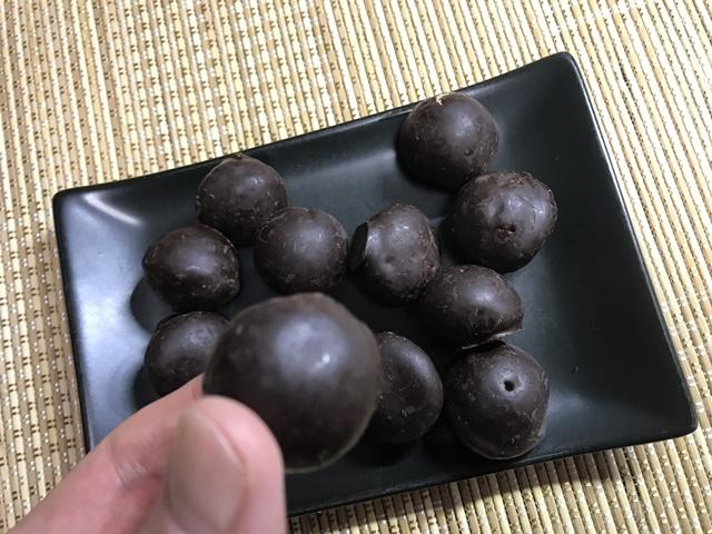 セブンプレミアム:チョコチップ入りのチョコ鈴カステラを指でつまんだところ