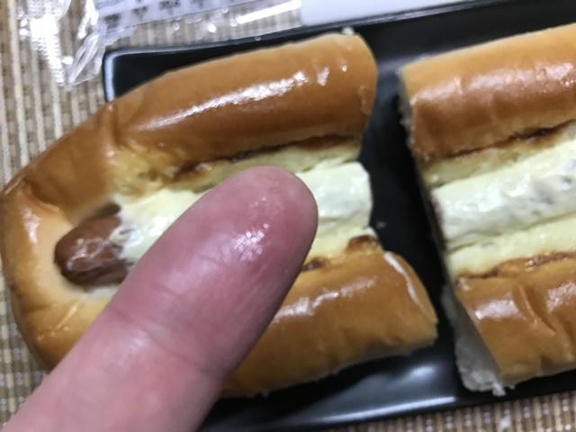 セブンプレミアム:食感のよいウインナーをはさんだ パリッと食感のウインナーパンをつまんでギトギトになった指