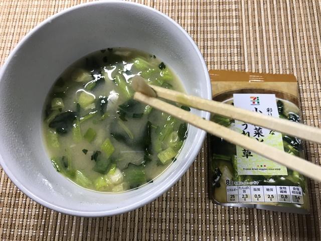 セブンプレミアム:彩り豊かな小松菜とほうれん草 味噌汁のネギを箸でつまんだところ